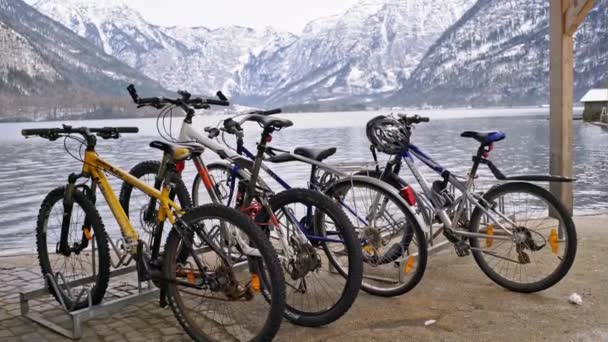 Modern road bikes parked at rack on pavement on lake shore with stunning snowy mountains on background in winter in Austrian Hallstatt
