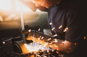 Photo Grinding steel with lot of sparks by worker in factory
