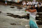 Salvador, bahia / brazil - 2020. február 2.: Yemanja bhaktája, gyertyatartó entitás látható, amint parfümöt kínál a Rio Vermelho strandon Salvadorban, a vallási ünnepség alatt..