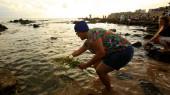Salvador, bahia / brazil - 2020. február 2.: jemanja bhaktája, gyertyafényes entitás látható, amint felajánlja az orixa virágot a rio Vermelho strandon Salvadorban a vallási ünnepség alatt.