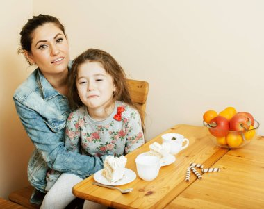 young mother with daughter on kitchen drinking tea together hugg