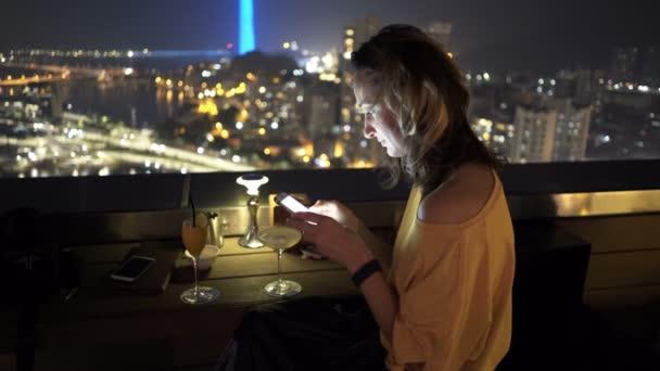 Mujer Joven Con Smartphone Beber Cóctel Sentado En La Terraza En Bar Por La Noche