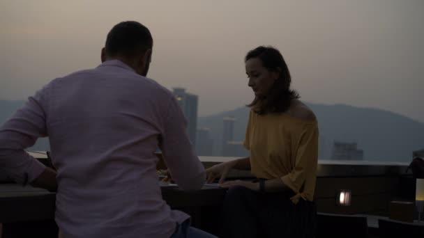 Joven Pareja Comer Bocadillo Sentado En Bar En La Terraza
