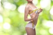 mladá dívka dělá tělo měření s krejčovským metrem