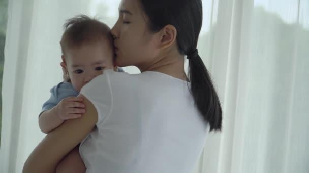 mladá asijská matka drží roztomilé dítě dcera polibky na tváře s láskou a něhou. Novorozená holčička roztomilá a veselá. koncept mateřství rodičovství dítě v jeslích láska a rodinný život