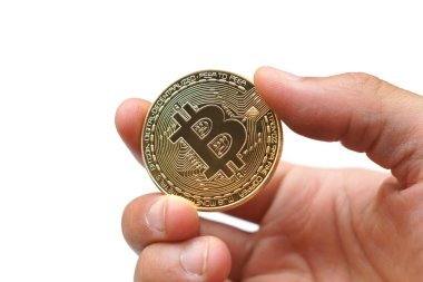Closeup of a hand holding a golden bitcoin isolated on white background