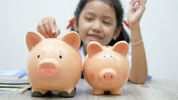 Asian little girl in Thai student uniform putting coin in to piggy bank shallow depth of field select focus at the pig