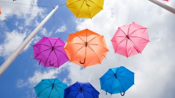 4K Bunter Regenschirm hängt vor wolkenlosem blauen Himmel