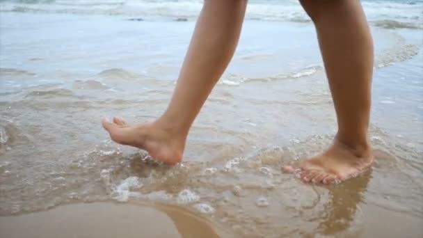 Slow motion žena nohy chůzi na písčité pláži s pobřeží vlna moře přírody pro letní dovolenou koncept