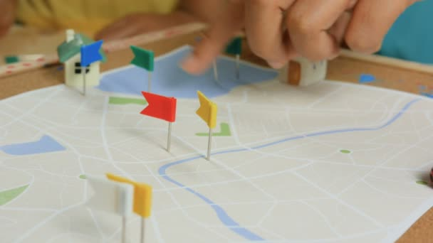 Close up shot hand of kids and mother pinning color pin at the map metaphor planning for transport and travel