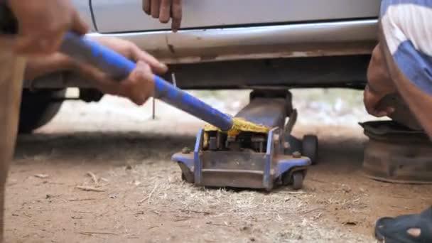 Rukou mechanik užívající vozu jack zvednout vůz opravit rameno lichoběžníkové a nahradit přední kolo auto