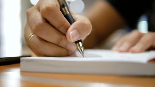 Nahaufnahme fotografierte Hände von Frauen, die auf Papier schreiben Notizbuch auswählen Fokus flache Schärfentiefe