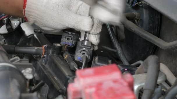 Zavřete mechanické ruce se otáčejí a opravují auto.