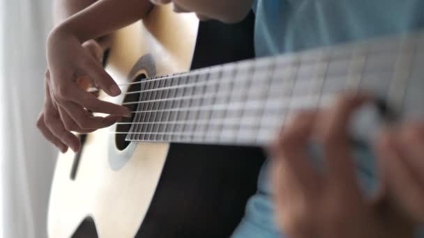 Detailní paže matky učí dceru jak hrát akustickou klasiku, hudba instrumentální pro jazz a snadno naslouchající hudební styl vybrat zaměření mělkou hloubku pole