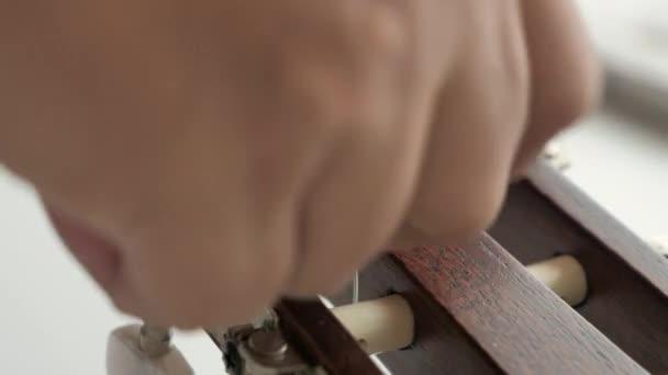Detailní ruce člověka, který nahrazuje akustickou klasickou kytaru pomocí nylonového a stříbrného řetězce pro jazz a snadno naslouchající hudební styl vybrat fokus mělkou hloubku pole