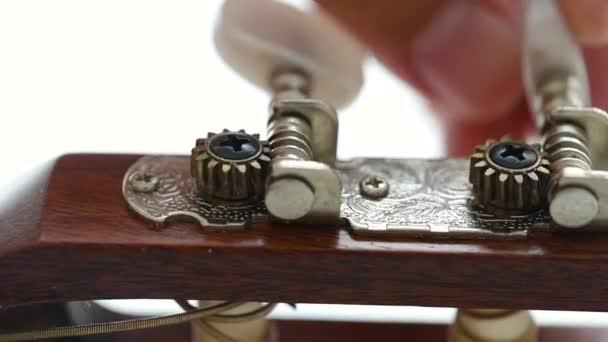 Közeli kezét az ember spinning tuner gomb akusztikus klasszikus gitár Finomhangolás a standard Key, zene instrumentális a jazz és a könnyű zenehallgatás zenei stílust válassza fókusz sekély mélységélesség