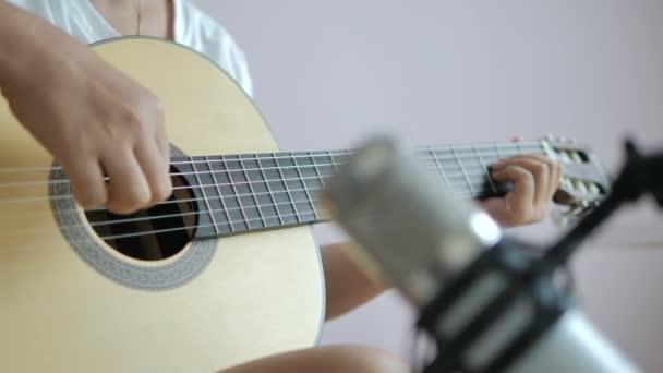 Detailní ruce ženy hrají akustickou klasickou kytaru a nahrávají s mikrofonem, hudba instrumentální pro jazz a snadno naslouchající hudba styl vybrat zaměření mělkou hloubku pole