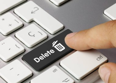 Delete Written on Black Key of Metallic Keyboard. Finger pressing key.
