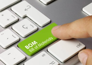BOM Bill of Materials Written on Green Key of Metallic Keyboard. Finger pressing key.