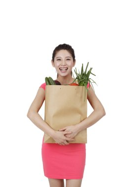 Young woman in pink dress holding shopping bag