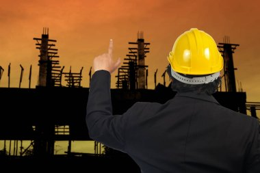 Engineer with yellow helmet point to building.