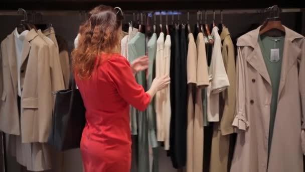 Mladá žena v červených šatech si vybírá oblečení v obchodě s oblečením.