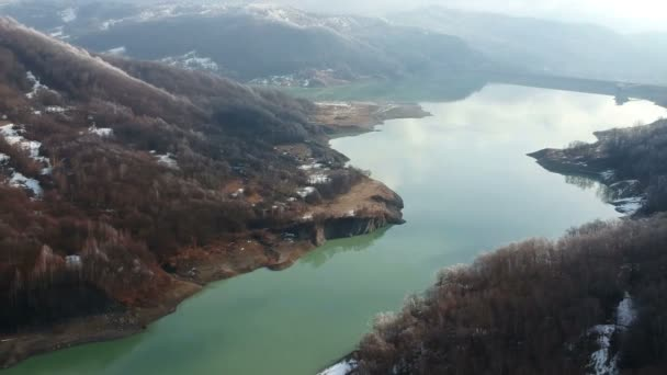 Water accumulation from a river valley in the mountains forming the lake of Maneciu  artificial dam , Prahova county, Romania, winter aerial scenery on a misty morning