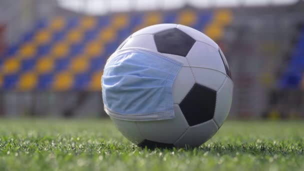 Coronavirus Pandemic Concept. Fotbalový míč v lékařské masce na prázdném stadionu