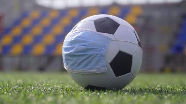 Coronavirus Pandemic Concept. Soccer Ball in Medical Mask at Empty Stadium