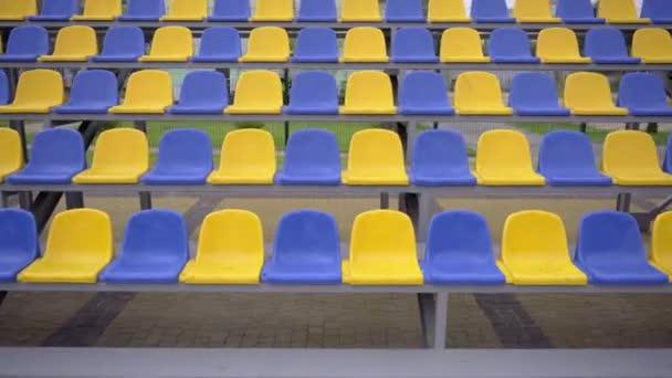 4k, üres sorok műanyag ülésekkel a stadionban. Sárga és kék helyek a Tribune of Sports Arénában nézők és rajongók nélkül