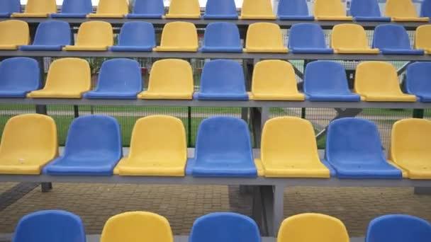 4k, Prázdné řady plastových sedadel na stadionu. Žlutá a modrá místa na tribuně sportovní arény bez diváků a fanoušků