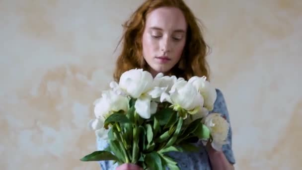 Close up portrait of beautiful red haired girl sniffs a big bush of white peonies