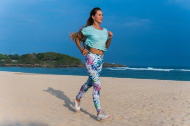 Woman running on beach at sunset. Beautiful fitness caucasian girl exercising outdoors on sea background. Caucasian fit model