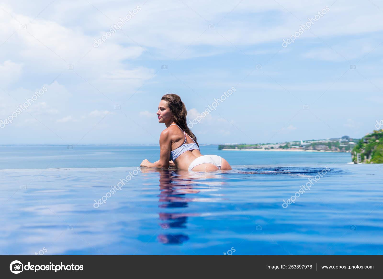 Nice Ass Butt sexy girl. beautiful woman. model lady bikini underwear big ass butt booty sit edge of water swim pool on the roof of luxury resort hotel nice sea