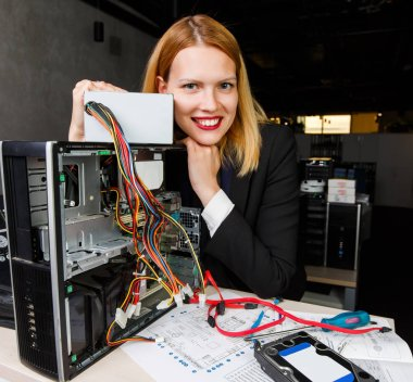 Photo of smiling woman at table next to broken processor