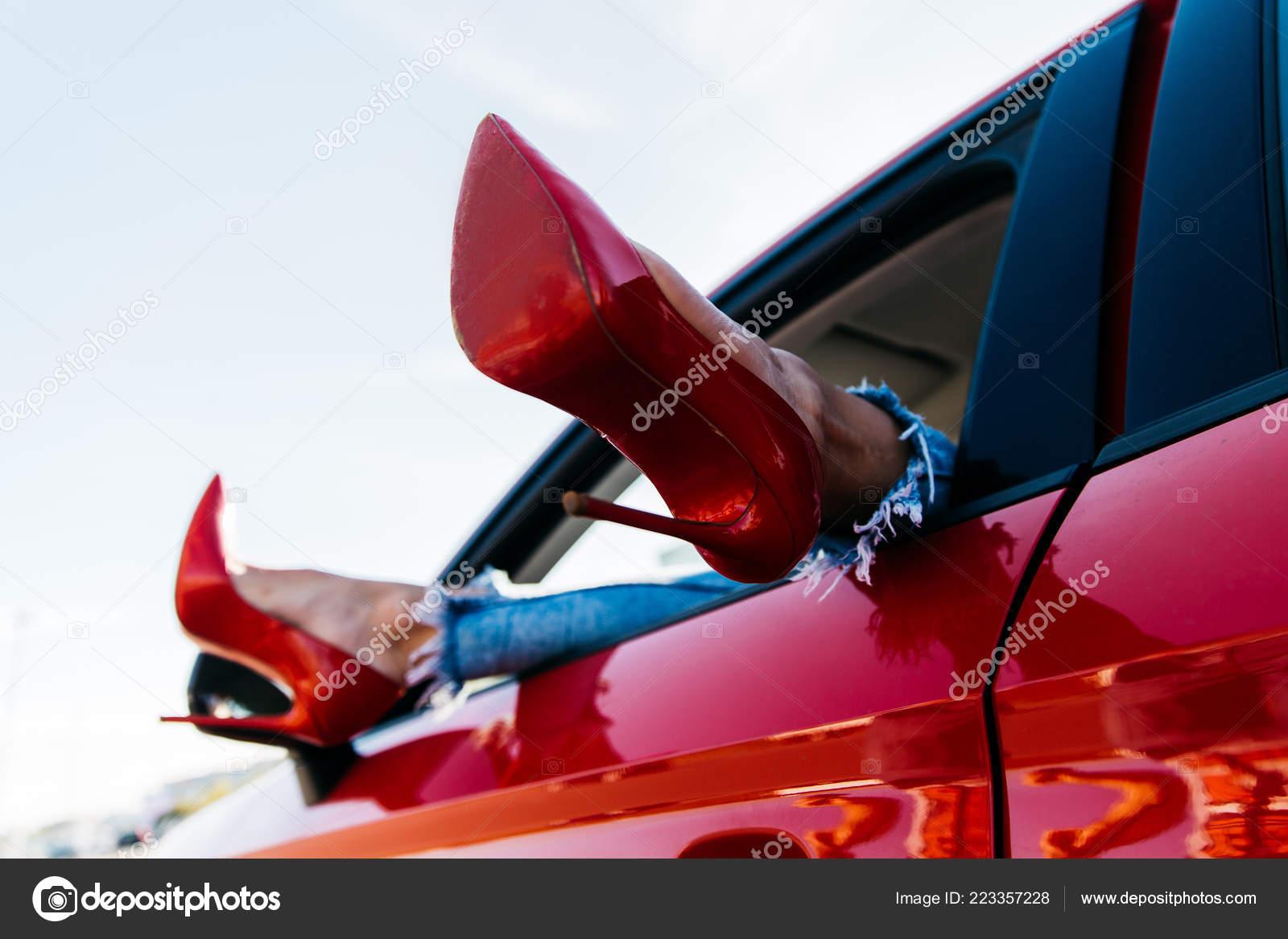 6077c91974 Fotos de piernas de mujer en zapatos rojos y los pantalones vaqueros que  sobresalen del coche
