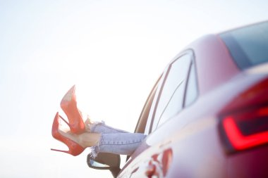 Photo of girls legs in red shoes sticking out of red car window