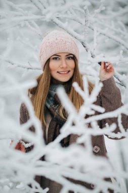 Portrait of smiling woman in hat on walk in winter forest