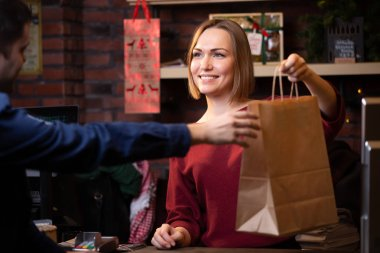 Photo of smiling seller woman giving paper bag to male buyer