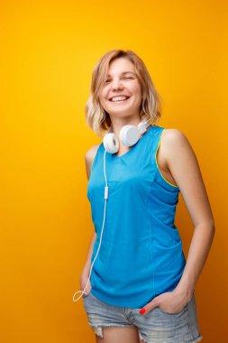 Photo of sport woman with headphones on empty orange background