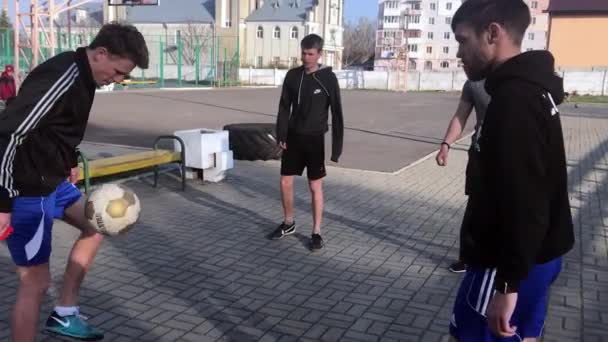 LVIV, UKRAINE - APRIL 14, 2019: A group of guys near the football field warming up before the game stuffing the ball.