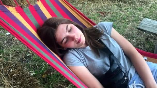 Beautiful, cute young girl on a summer day resting on a colored hammock in a park or outdoors