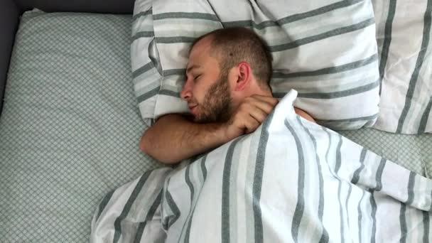 Felülnézet a fiatalember alszik az ágyban.