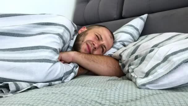 Člověk spí v posteli sám pod dekou. Boční pohled.