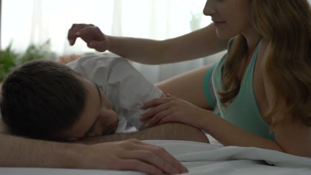 Young wife kissing sleeping husband on cheek in morning, romantic honeymoon