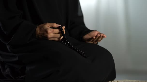 Praying woman with traditional islamic beads in hand kneeling on rug in  mosque