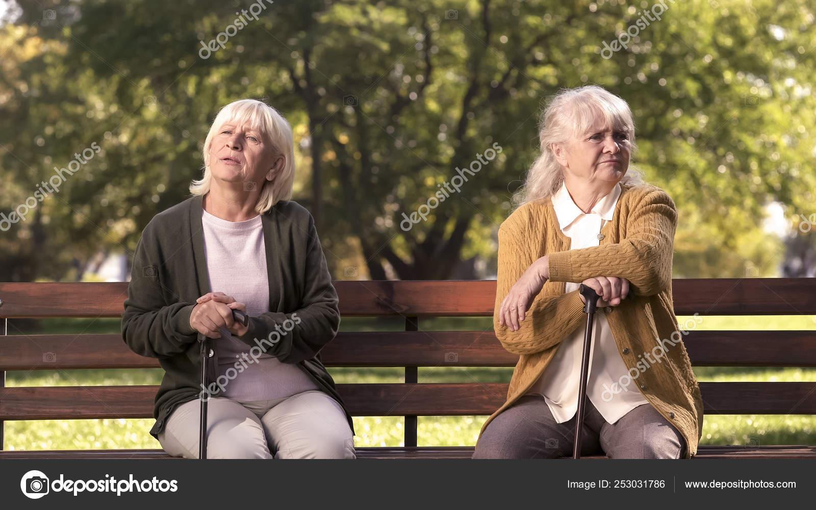 Abuelas Maduras maduras sentadas por separado banco parque amigos