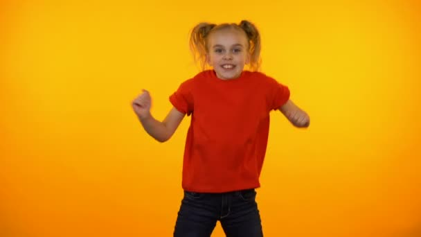 Funny preteen girl dancing to music, active child having fun, orange  background