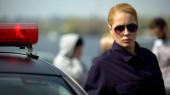 Koncentrált női tiszt állandó közelében rendőrautó, baleset a háttérben