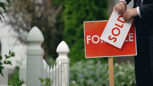 Real estate agent puts sold inscription on for sale signboard, successful deal